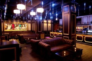 Posh lounge room with drip LED lights, rich wallpaper and chandeliers